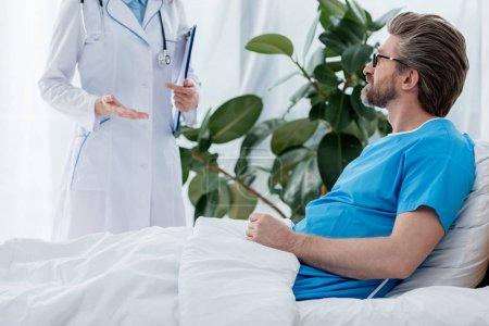 Photo pour Crochet vue d'un médecin en blouson blanc parler à un patient à l'hôpital - image libre de droit