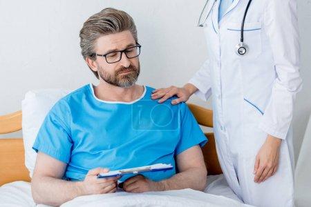 """Photo pour Crochet vue d'un médecin en manteau blanc touchant l """"épaule d'un patient triste avec une planche à pince - image libre de droit"""