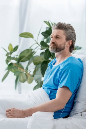 Photo for Handsome patient in medical gown looking away in hospital - Royalty Free Image