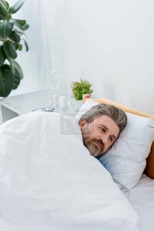 Photo pour Vue à angle élevé d'un patient en blouse médicale allongé au lit - image libre de droit