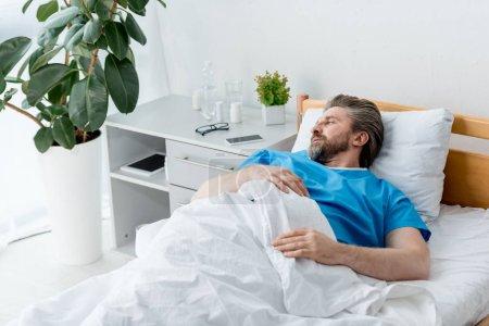 Photo pour Vue à angle élevé d'un patient en blouse médicale étendu et regardant loin à l'hôpital - image libre de droit
