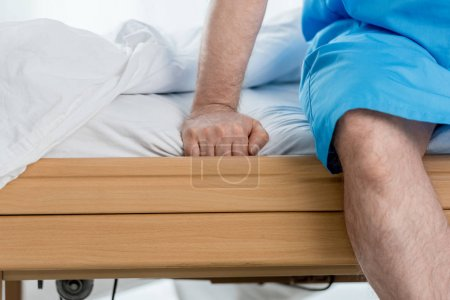 cropped view of patient in medical gown sitting on bed in hospital