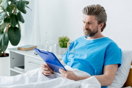 Photo for Patient in medical gown looking at clipboard in hospital - Royalty Free Image