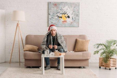 Photo pour Homme malade en chapeau de santa, enveloppé dans une couverture, assis sur un canapé près de la table avec des médicaments - image libre de droit