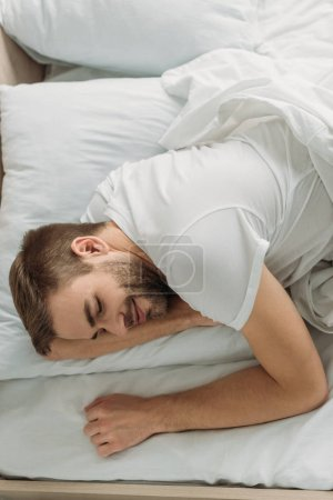 Photo for Overhead view of young man smiling while sleeping on white bedding - Royalty Free Image