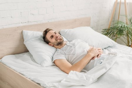 Photo for Young man lying in bed and suffering from abdominal pain - Royalty Free Image