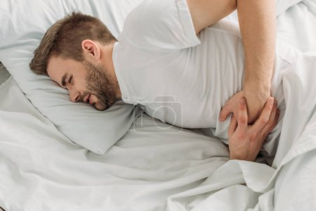Photo for Young man lying in bed and suffering from stomach pain with closed eyes - Royalty Free Image