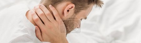 Photo for Panoramic shot of young man suffering from neck pain - Royalty Free Image