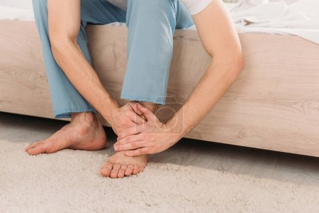 Photo for Cropped view of man sitting on bed and suffering from pain in leg - Royalty Free Image