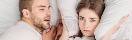 Photo pour Top view of woman exhausted plugging ears with pillow while lying in bed near sniving husband, panoramic shot - image libre de droit