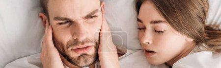 Photo for Top view of exhausted man plugging ears with hands while lying in bed near snoring wife, panoramic shot - Royalty Free Image