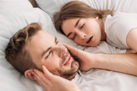 Photo for Exhausted man plugging ears with hands while lying in bed near snoring wife - Royalty Free Image