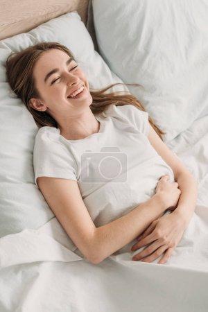 Photo pour Gaie fille rire tout en étant couché dans le lit et tenant la main sur l'estomac - image libre de droit