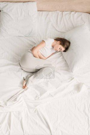 Photo pour Vue du haut de la fille couchée au lit avec les yeux fermés et souffrant de douleurs abdominales - image libre de droit