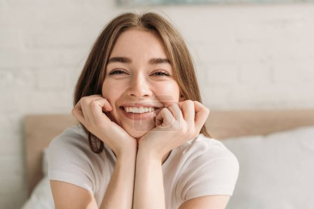 Photo pour Jeune femme joyeuse qui rit à la caméra en tenant la main près du visage - image libre de droit