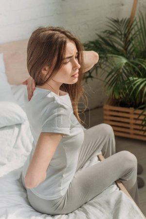 Photo pour Jeune femme assise au lit et souffrant de maux de dos - image libre de droit