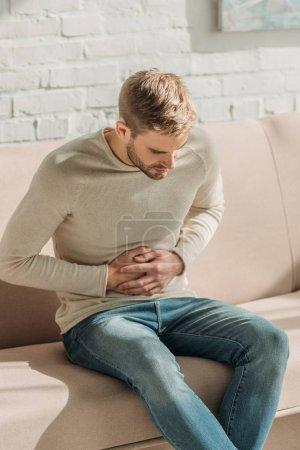 Photo pour Jeune homme assis sur le canapé à la maison et souffrant de douleurs à l'estomac - image libre de droit