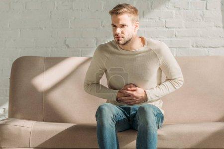 Photo pour Bouleversé homme assis sur le canapé et toucher l'estomac tout en souffrant de douleurs abdominales - image libre de droit