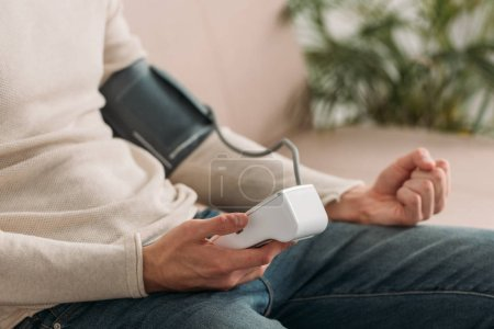 Photo for Cropped view of man sitting on sofa at home and using tonometer - Royalty Free Image