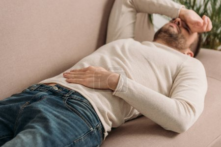 Photo for Selective focus of man lying on sofa and suffering from headache - Royalty Free Image