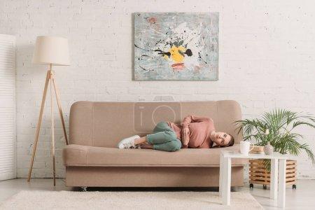 Photo pour Jeune femme allongée sur le canapé tout en souffrant de douleurs abdominales - image libre de droit