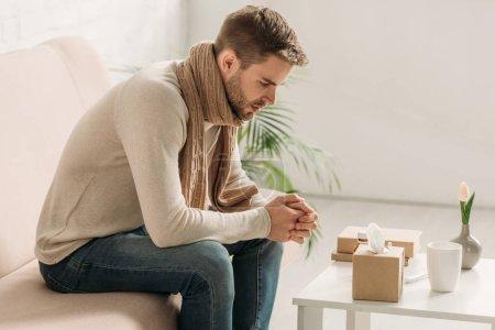 Photo pour Malade en écharpe chaude et pull assis sur le canapé près de la table avec des médicaments - image libre de droit