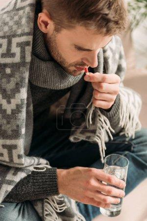 Photo pour Homme malade, enveloppé dans une couverture, tenant un verre d'eau tout en prenant des médicaments - image libre de droit