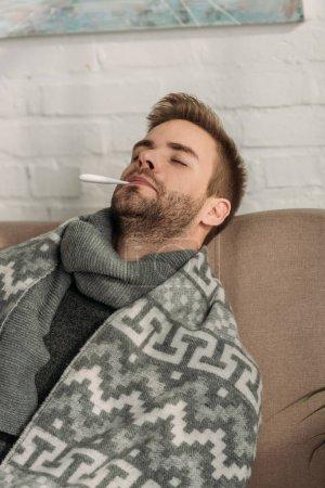 Photo pour Malade, enveloppé dans une couverture, assis sur un canapé les yeux fermés et mesurant la température - image libre de droit