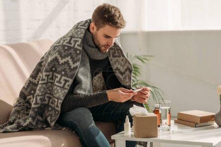 Photo pour Malade, enveloppé dans une couverture, assis sur un canapé et regardant un thermomètre - image libre de droit