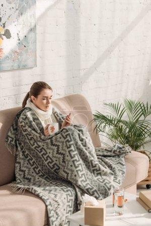 Foto de Chica enferma, envuelta en manta, mirando al termómetro y tomando una taza de bebida caliente. - Imagen libre de derechos