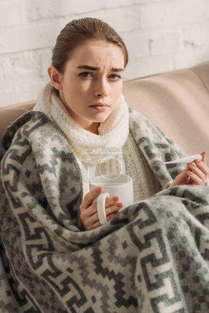 Photo pour Fille malade, enveloppé dans une couverture, regardant la caméra tout en tenant thermomètre et tasse de boisson chauffante - image libre de droit
