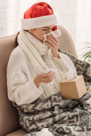 Photo pour Malade femme éternuer dans napking tandis que assis sur canapé dans santa chapeau - image libre de droit