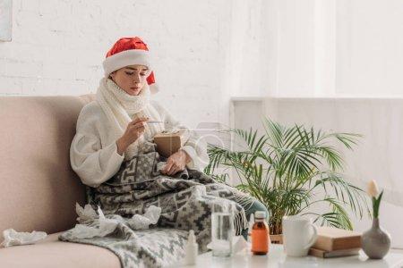 Photo pour Femme malade dans le chapeau de Père Noël, enveloppé dans la couverture, assis sur le canapé près de la table avec des médicaments et regardant le thermomètre - image libre de droit