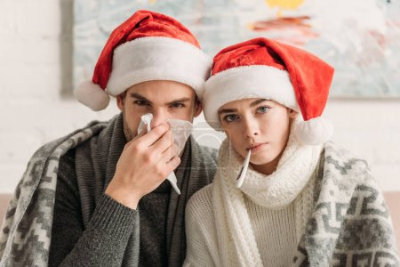 Photo for Diseased couple wearing santa hats and covered with blanket looking at camera - Royalty Free Image