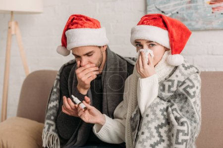 Photo pour Femme malade avec nez qui coule en regardant la caméra tout en donnant pulvérisation nasale au petit ami malade - image libre de droit