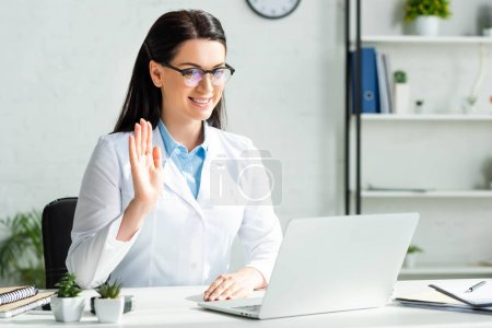 Photo for Smiling doctor waving and having online consultation with patient on laptop in clinic office - Royalty Free Image