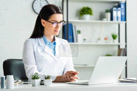 Photo pour Un médecin sûr d'avoir une consultation en ligne avec le patient sur un ordinateur portable au bureau de la clinique - image libre de droit