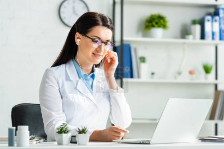 Photo pour Femme médecin souriant avec écouteurs consultation en ligne avec la patiente sur ordinateur portable dans le bureau de la clinique - image libre de droit