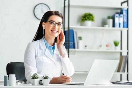 Photo pour Un médecin gai dans un écouteur lors d'une consultation en ligne avec un patient sur un ordinateur portable au bureau de la clinique - image libre de droit