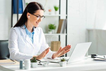 Photo pour Attrayant médecin souriant ayant consultation en ligne avec le patient sur ordinateur portable dans le bureau de la clinique - image libre de droit