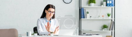 Photo pour Photo panoramique d'un médecin professionnel dans un écouteur ayant une consultation en ligne avec le patient sur un ordinateur portable dans le bureau de la clinique - image libre de droit
