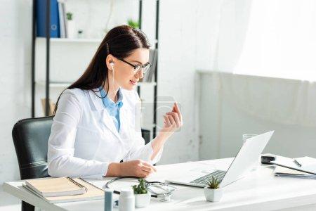 Photo pour Une femme médecin séropositive dans un écouteur lors d'une consultation en ligne avec une patiente sur un ordinateur portable dans un cabinet médical - image libre de droit