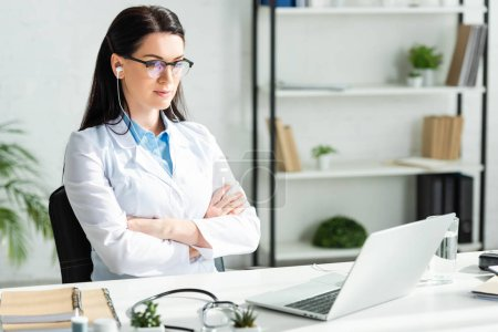 Photo for Female doctor with crossed arms having online consultation with patient on laptop in clinic office - Royalty Free Image