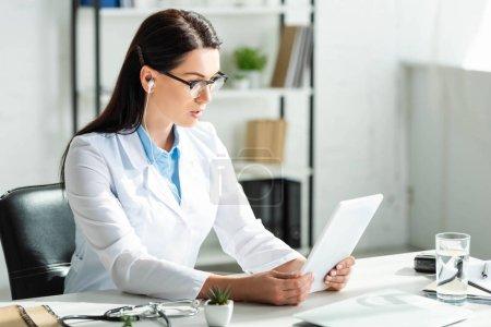 Photo pour Médecin intéressé aux écouteurs ayant la consultation en ligne sur comprimé numérique dans le bureau de la clinique avec ordinateur portable - image libre de droit