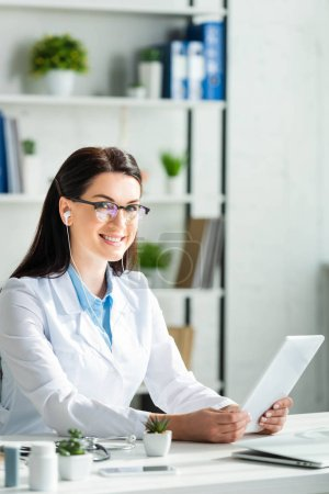 Photo for Positive doctor having online consultation on digital tablet in clinic office with laptop - Royalty Free Image