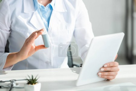 Photo for Cropped view of doctor showing pills to patient on online consultation on digital tablet in office - Royalty Free Image