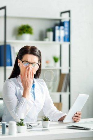 Photo pour Les médecins fatigués bavardant et ayant la consultation en ligne sur les comprimés numériques dans le bureau de la clinique - image libre de droit
