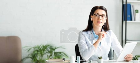 Photo for Panoramic shot of thoughtful doctor in earphones having online consultation on digital tablet in office - Royalty Free Image