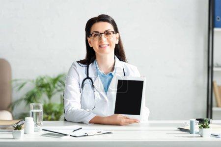 Photo pour Beau médecin souriant montrant un comprimé numérique avec écran vierge dans le bureau de la clinique - image libre de droit
