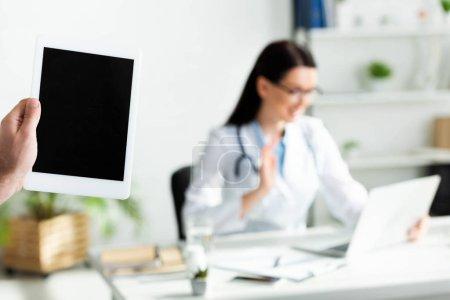Photo pour Crochet vue d'un homme tenant un comprimé numérique avec écran vierge dans le bureau de la clinique avec consultation en ligne du médecin sur un ordinateur portatif - image libre de droit